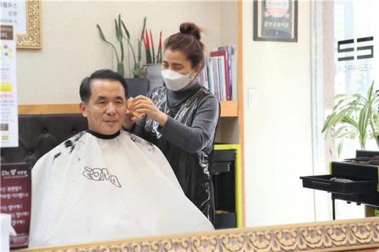 Korea Deposit Insurance Corp. (KDIC) CEO Wi Seong-bak, left, gets a haircut at a small beauty salon in Seoul, Monday, as part of the state-run firm's campaign to support small businesses having difficulty due to the COVID-19 pandemic. The KDIC previously helped the beauty parlor's owner reschedule her debt. / Courtesy of KDIC