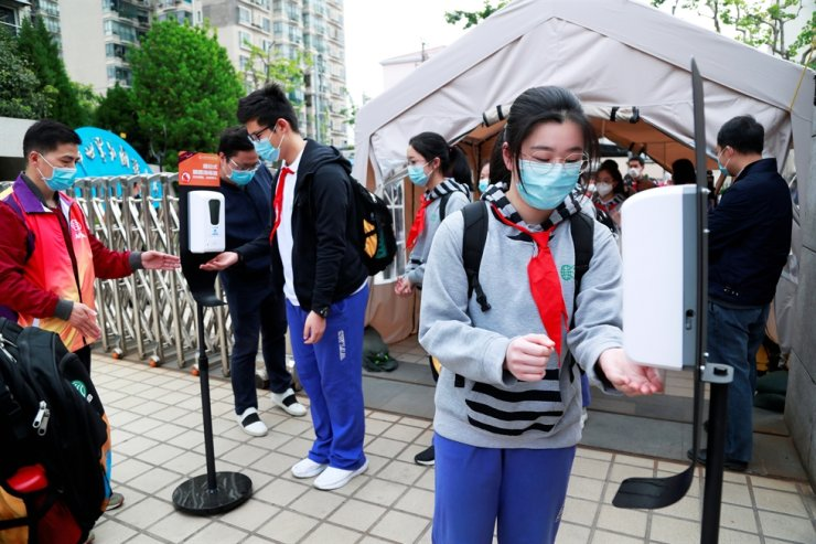 Students wearing face masks use hand sanitizers at an entrance to a school in Shanghai, China, as senior high school and senior middle school students in Shanghai return to campus following the coronavirus disease (COVID-19) outbreak, Monday. /Reuters