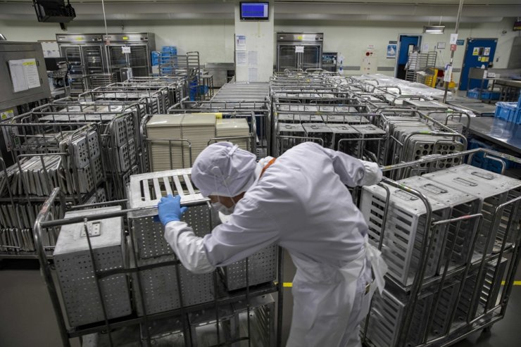 A worker moves piles of empty meal carts at an in-flight meal production facility operated by Korean Air in Incheon, Thursday. / Korea Times photo by Shim Hyun-chul