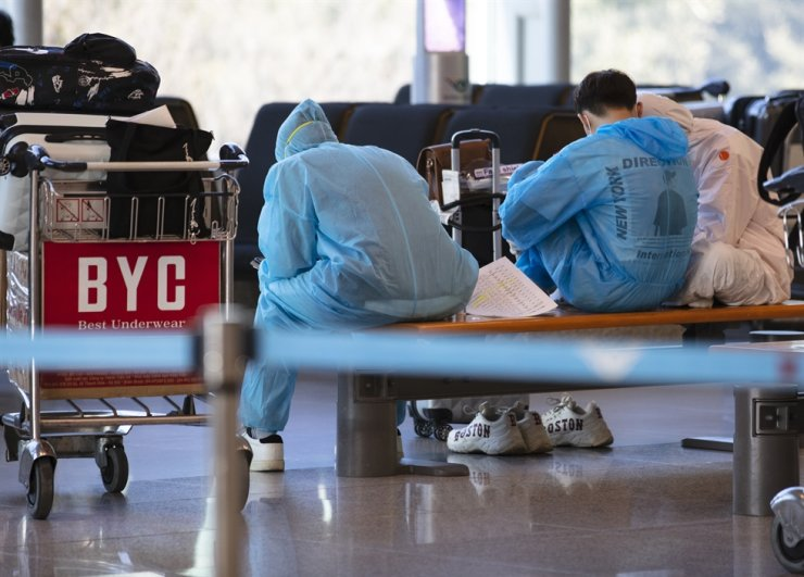 People wearing protective clothing sit on a bench at Incheon International Airport, Monday. Yonhap