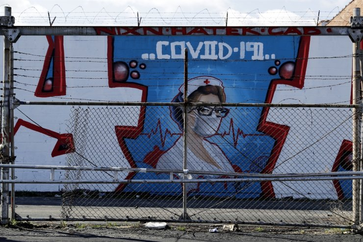 A COVID-19 mural is seen in Chicago Logan Square, Friday, April 10. AP