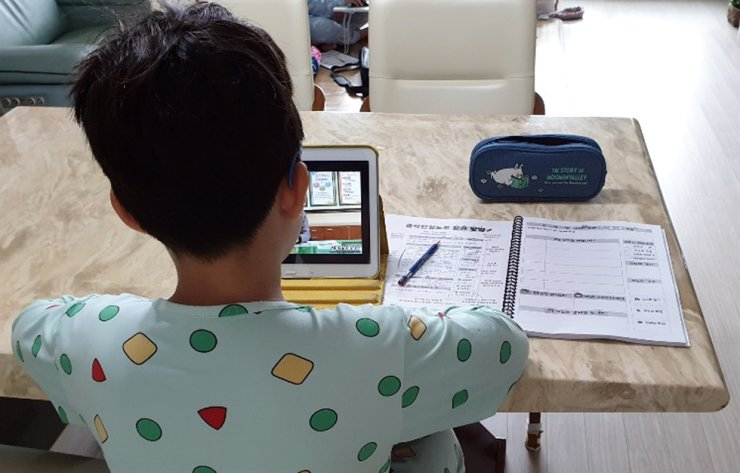 A third grader in Jeonju, North Jeolla Province, watches a lecture on a tablet PC at home. /Yonhap