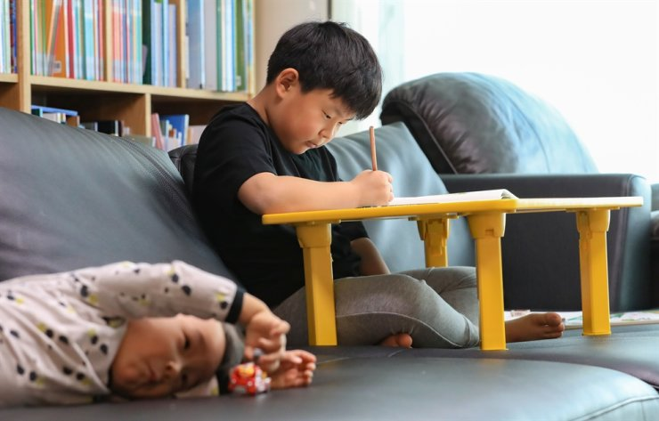 A second grader in Guri, Gyeonggi Province, watches a math lecture on EBS at home. /Yonhap