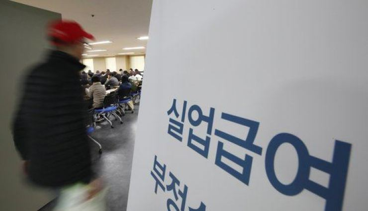 A man walks into a crowded room to learn how to receive unemployment benefits. Yonhap