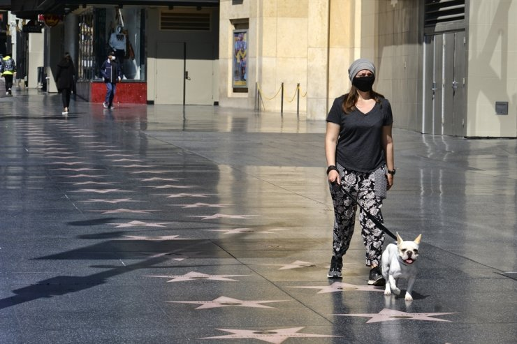 A woman wearing a mask to protect from COVID-19 walks her dog along and empty Hollywood Boulevard on Tuesday, April 21, 2020, in the Hollywood section of Los Angeles. AP