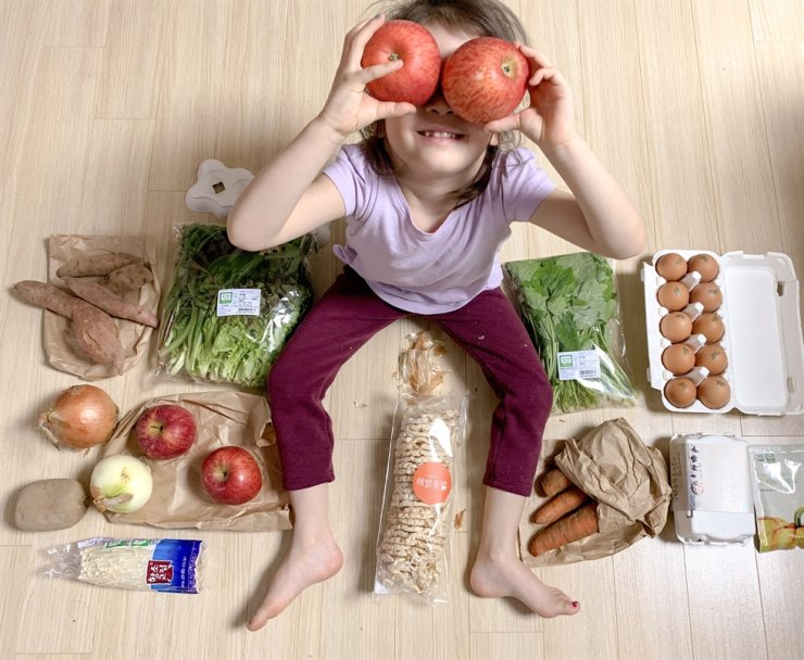 A child sits with a selection of food from a Slowbox delivery. Photo courtesy of Hallie Bradley