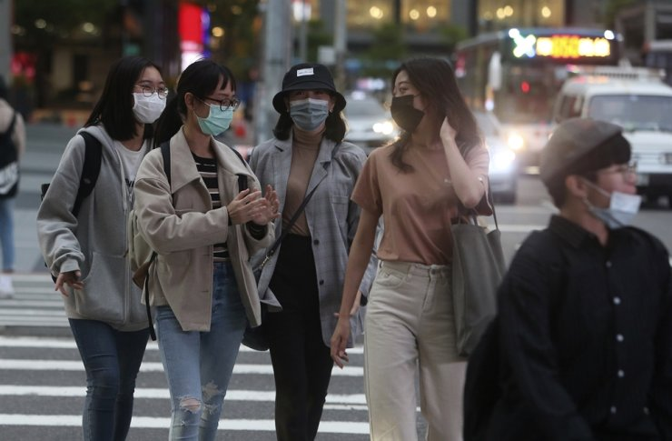 Pedestrians wear face masks to protect against the spread of the coronavirus on the streets of Taipei, Taiwan, Tuesday, March 31, 2020. AP