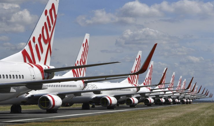 In this April 7, 2020, photo, grounded Virgin Australia aircraft are parked at Brisbane Airport in Brisbane, Australia. Virgin Australia, the nation's second-largest airline, announced on April 21 that it had entered voluntary administration as it seeks to strengthen its finances amid a debt crisis. AP