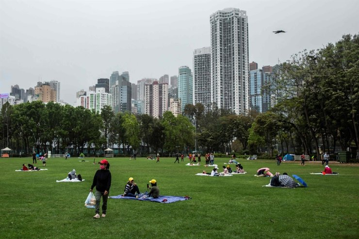People adhering to new social distancing measures gather in Victoria Park in Hong Kong on March 29, 2020. AFP