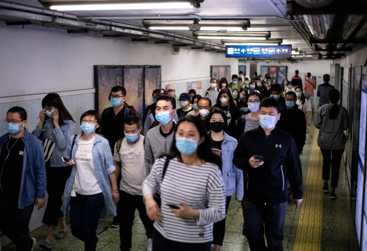 People wearing face masks amid concerns of the COVID-19 pandemic commute through a subway station in Beijing on May 13, 2020. AFP