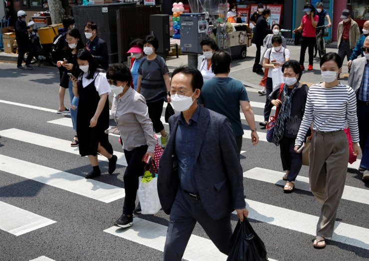 Pedestrians in face masks cross a street, amid the spread of the coronavirus, in Seoul, May 28, 2020. Reuters