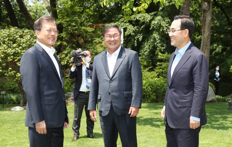 President Moon Jae-in stands with ruling Democratic Party of Korea floor leader Rep. Kim Tae-nyeon, center, and main opposition United Future Party floor leader Rep. Joo Ho-young, right, before their luncheon at Cheong Wa Dae, Thursday. /Yonhap