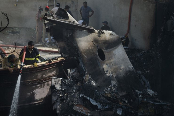 A firefighter sprays water on the wreckage of a Pakistan International Airlines aircraft, with nearly 100 people on board, that crashed in a residential area in Karachi, Friday, also killing several people on the ground. AFP
