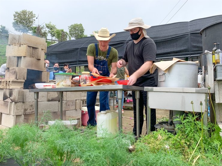 Ryan Phillips, left, is assisted as he prepares lamb pitas for farm guests, May 16. Image courtesy of Hallie Bradley
