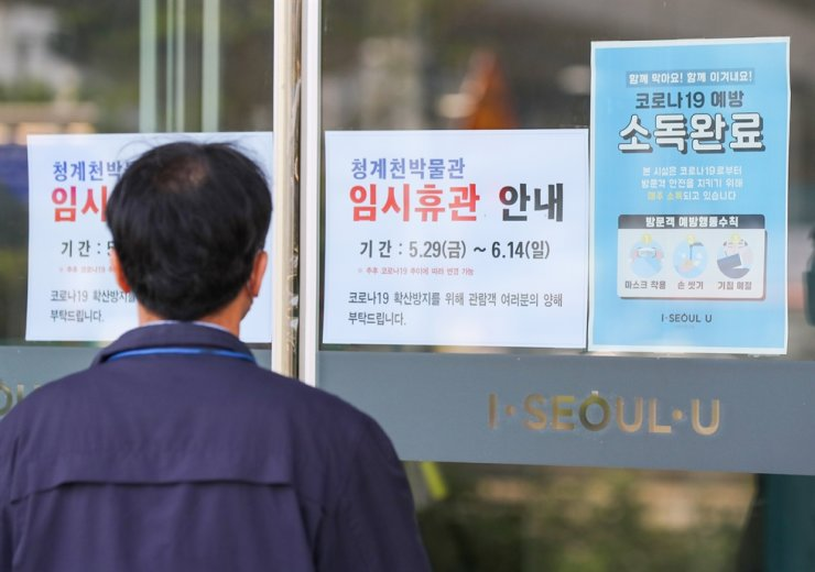 A closure notice hangs on the main entrance of the Cheong Gye Cheon Museum in Seoul, Friday. The government has closed state-run museums, galleries and theaters in Seoul and surrounding areas for two weeks in a precautionary measure after a recent resurgence in coronavirus cases linked to a logistics center in the metropolitan region. Yonhap