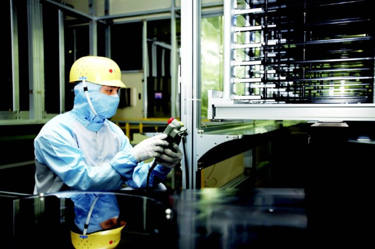 A researcher at LG Display inspects the activity of a robot delivering glass sheets using a remote controller at the company's cutting-edge LCD manufacturing facility in Paju, Gyeonggi Province, in this file photo. Korea Times file