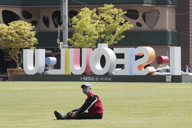 A man wearing a face mask to help protect against the spread of the new coronavirus takes a rest on the grass at Seoul Plaza in Seoul, Thursday, May 21, 2020. AP