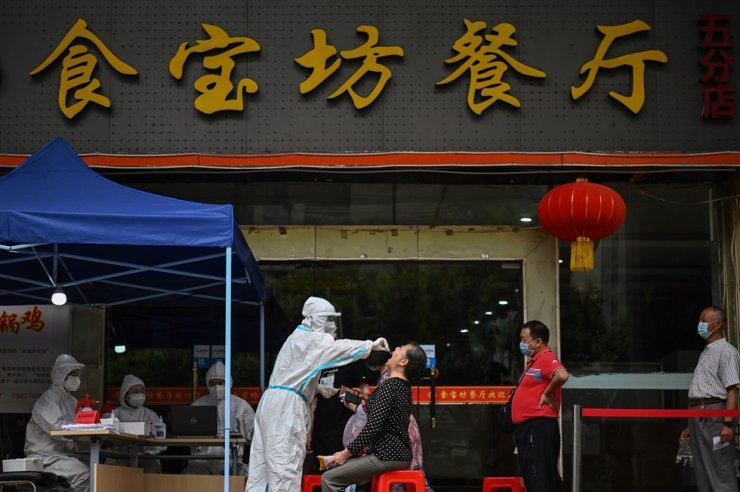 A medical worker takes a swab sample from a woman to be tested for the coronavirus next to a street in Wuhan, in China?s central Hubei province on May 16, 2020. AFP