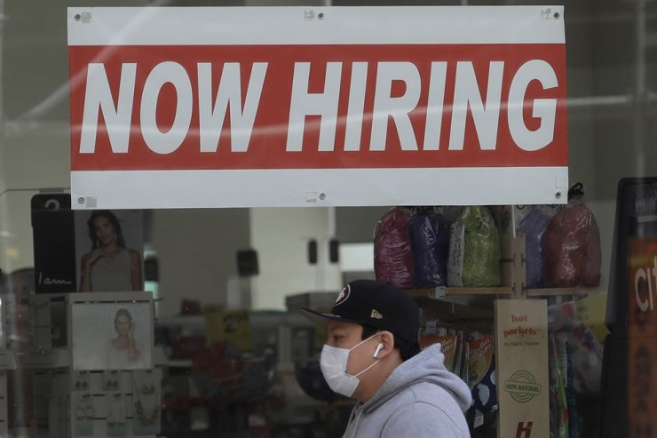 A man wears a mask during the coronavirus outbreak while walking under a 'Now Hiring' sign at a CVS Pharmacy in San Francisco, May 7. AP