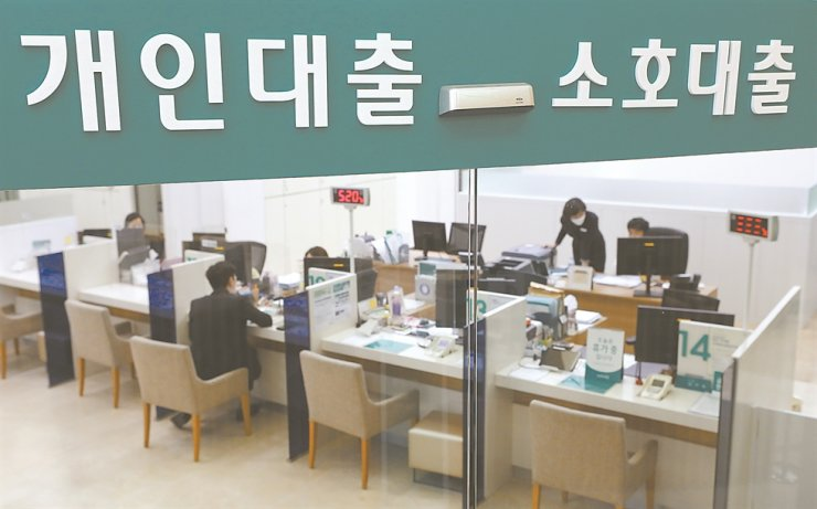 A loan seeker sits in front of a teller at a branch of Hana Bank in Seoul, April 20. The Korea Times file
