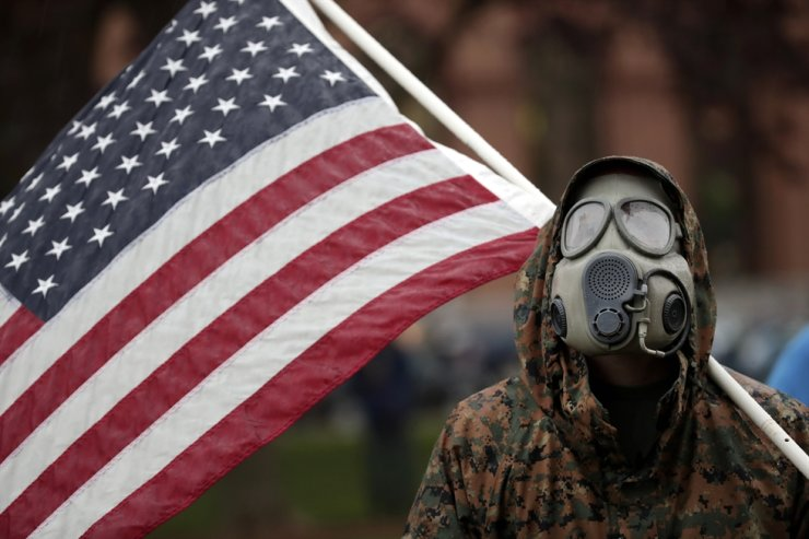 A protester wears a gas mask and carries an American flag during a rally in response to Michigan's coronavirus stay-at-home order, at the State Capitol in Lansing, Mich., Thursday, May 14. AP