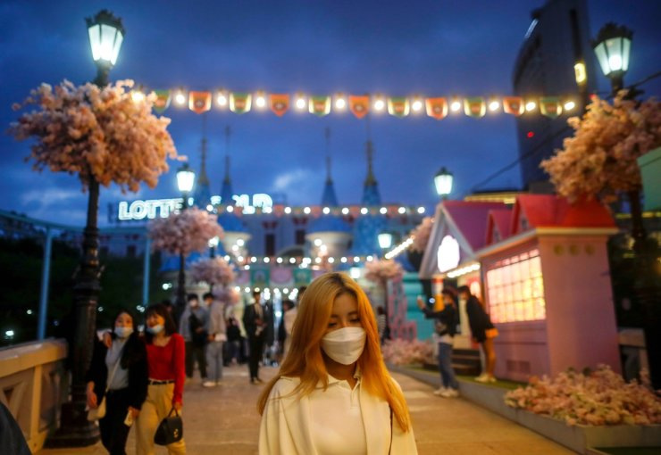A woman wearing a protective face mask to avoid the spread of COVID-19 looks on at an amusement park in Seoul, April 30, 2020. Reuters