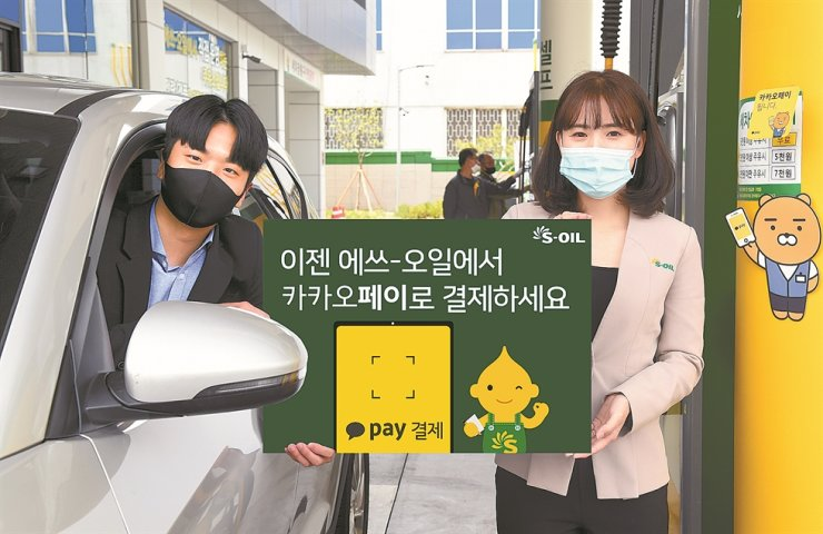 Models hold a sign that reads 'Kakao Pay can be used at S-OIL' as the oil company becomes the first to implement the Kakao payment system at its gas stations nationwide. Customers will be able to use a Kakao Pay barcode when filling their gas tanks. / Courtesy of S-OIL