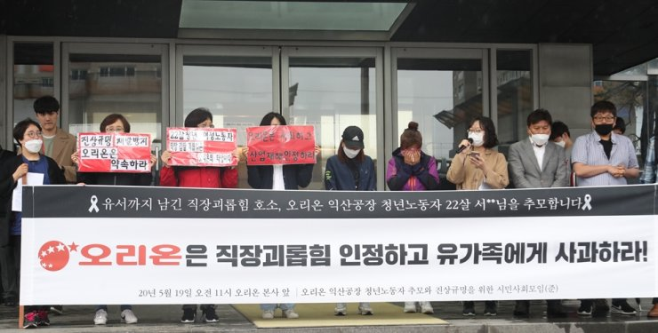 Members of a civic group rally in front of Orion Group's building in Yongsan-gu, Seoul, Tuesday, to condemn the company's ignorance of workplace bullying. /Yonhap