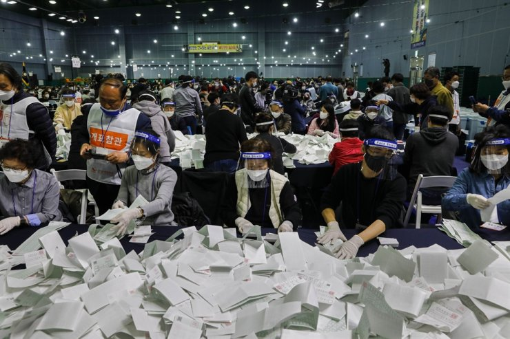 People sort ballots for the general election before sending them to machines designed to tabulate votes at a multi-purpose badminton stadium in Yeongdeungpo District, Seoul after polls closed April 15. / Korea Times photo by Shim Hyun-chul