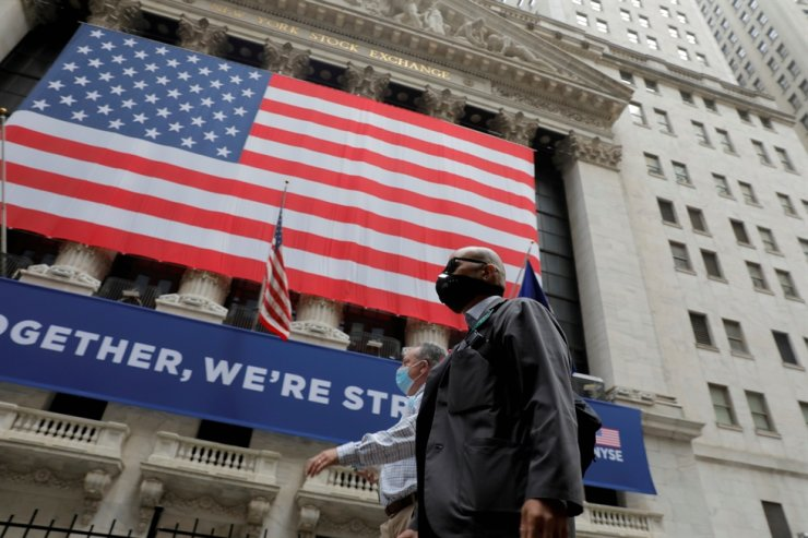 Traders walk past the New York Stock Exchange as the building opens for the first time since March while the COVID-19 pandemic continues in the Manhattan borough of New York, U.S., May 26, 2020. Reuters
