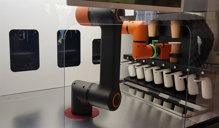 A robot picks up a cup containing coffee to serve at the world's first 24-hour unmanned coffee shop, called 'Storant,' which opened in Yuseong-gu, Daejeon Metropolitan City, May 15. Here, robots receive orders, make coffee and deliver drinks to customers. / Yonhap