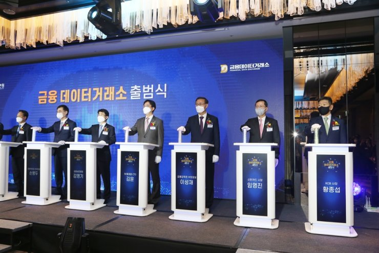 Shinhan Card CEO Lim Young-jin, second from right, and other participants in the opening ceremony of the Financial Data Exchange push buttons at the Four Seasons Hotel Seoul, Monday. Lim is in charge of Shinhan Financial Group's big data business. / Court