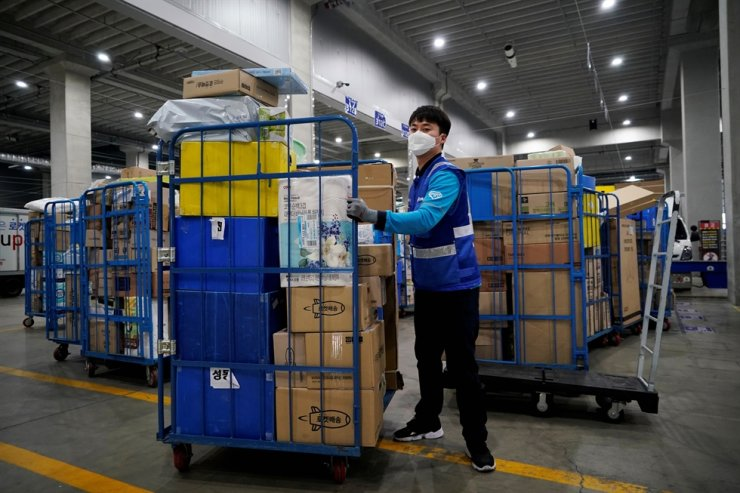 File picture of a delivery man for Coupang wearing a mask to prevent contracting the coronavirus, loading packages before leaving to deliver them in Incheon, South Korea, March 3, 2020. Reuters