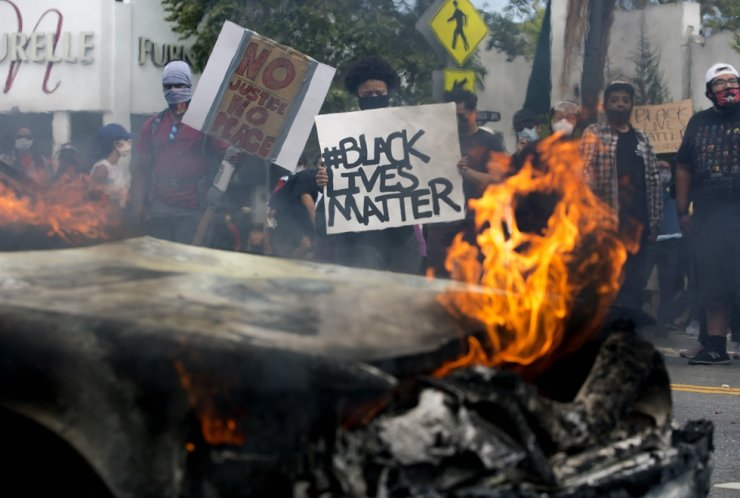 People hold signs and shout behind a burning police vehicle in Los Angeles, Saturday, May 30, 2020, during a protest over the death of George Floyd. AP