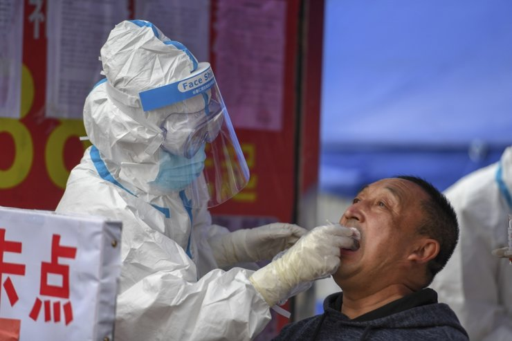 In this May 17, 2020, photo released by Xinhua News Agency, a medical worker collects a sample for COVID-19 testing at the Tongji community in Shulan in northeastern China's Jilin Province. Authorities have tightened restrictions in parts of Jilin province in response to a local cluster. AP-Yonhap