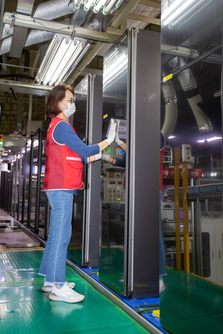 An employee at an LG Electronics plant in Changwon, South Gyeongsang Province, helps manufacture the company's Tromm Styler steam clothing care system in this May 25 photo. LG Electronics said sales of the large Tromm Styler throughout this year grew 30 percent from a year earlier. Courtesy of LG Electronics
