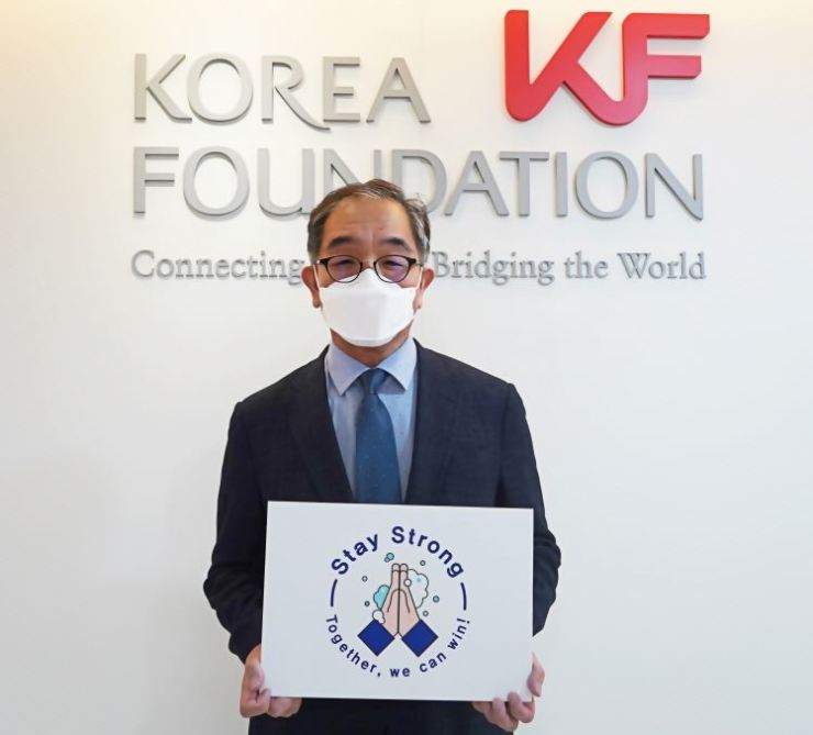 Korea Foundation (KF) President Lee Geun holds a poster for a campaign against COVID-19 entitled 'Stay Strong – Together, we can win!' at his office in Seoul, April 29. The Ministry of Foreign Affairs, which runs the foundation aimed at public diplomacy, initiated the campaign. / Courtesy of KF
