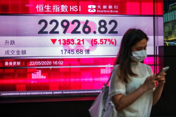 A woman stands in front of a panel displaying the afternoon trading on the Hang Seng Index, after Beijing's plans to impose national security legislation in Hong Kong, May 22, 2020. Reuters