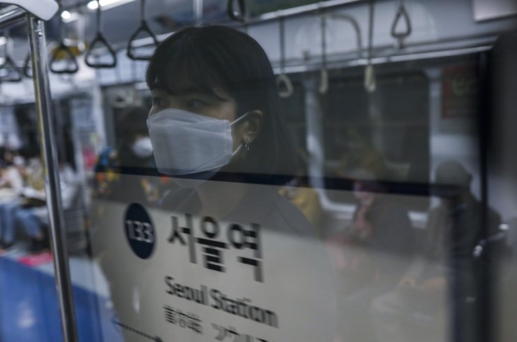 A subway passenger wearing a mask looks out through a window at Seoul Station. Korea Times photo by Shim Hyun-chul