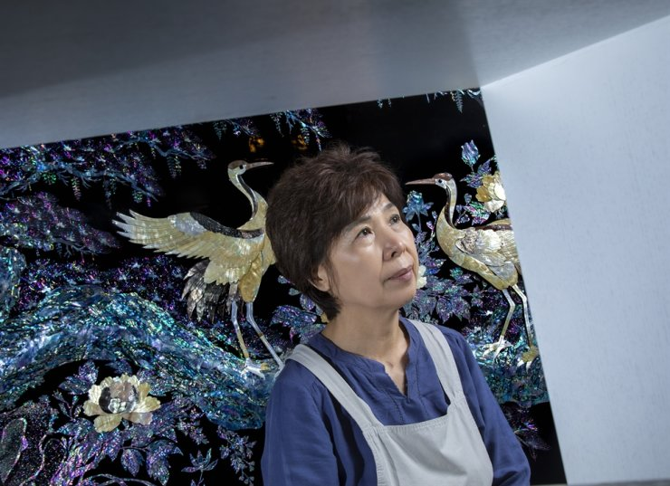 Mother-of-pearl craftsperson Lee Young-ok poses in front of her mother-of-pearl partition featuring cranes at her studio in Gwangju, Gyeonggi Province, Wednesday. Korea Times photo by Shim Hyun-chul