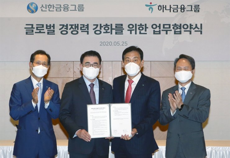 Shinhan Financial Group Chairman Cho Yong-byoung, second from left, and Hana Financial Group Chairman Kim Jung-tai, second from right, hold a memorandum of understanding regarding their partnership in the global market at Lotte Hotel in downtown Seoul, Monday. From left are Hana Bank CEO Ji Sung-kyoo, Cho, Kim and Shinhan Bank CEO Jin Ok-dong. / Courtesy of Shinhan, Hana financial groups