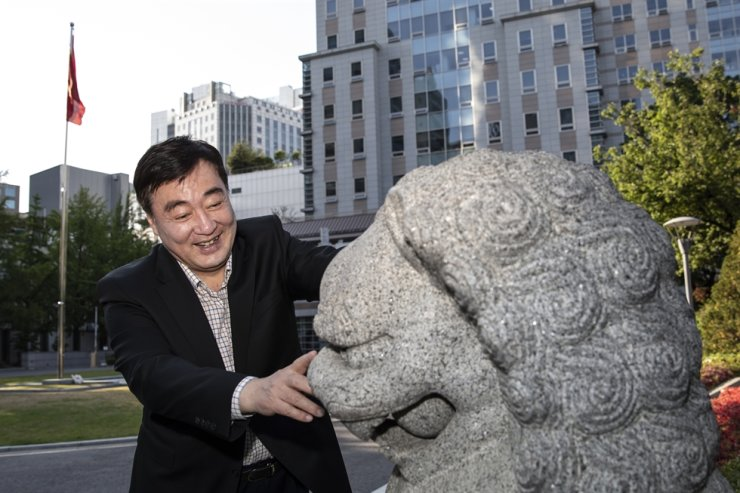 Xing Haiming touches a lion statue that has stood at the Chinese Embassy in Seoul for 28 years, Wednesday. Korea Times photo by Choi Won-suk