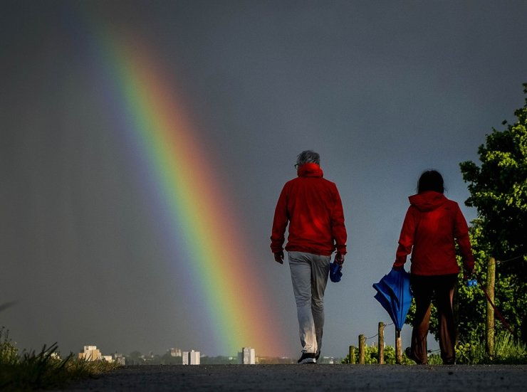 A couple walk on a small path towards a rainbow in the sky over Frankfurt, Germany, that appears after a heavy rain shower Saturday, May 2, 2020. /AP