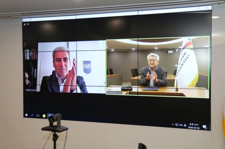 World Taekwondo and Taekwondo Humanitarian Foundation President Choue Chung-won, right, and Union Internationale Motonautique President Raffaele Chiulli applaud after signing a memorandum of understanding during their online video conference, Wednesday. Courtesy of World Taekwondo