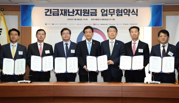 Financial Services Commission Chairman Eun Sug-soo, fifth from left, Minister of the Interior and Safety Chin Young, fourth from left, and the CEOs of credit card firms hold copies of an agreement regarding government-provided emergency relief money at the Government Complex Seoul, May 8. / Courtesy of Ministry of the Interior and Safety