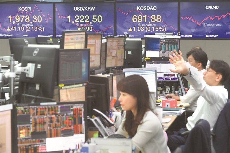 Traders watch computer monitors at KEB Hana Bank headquarters in central Seoul, Tuesday, as Korea's benchmark KOSPI started strong along with rallies in other global stock markets over hopes for a COVID-19 vaccine. The Seoul stock index closed at 1,980.61, up 43.50 points or 2.25 percent from the previous trading day. / Yonhap