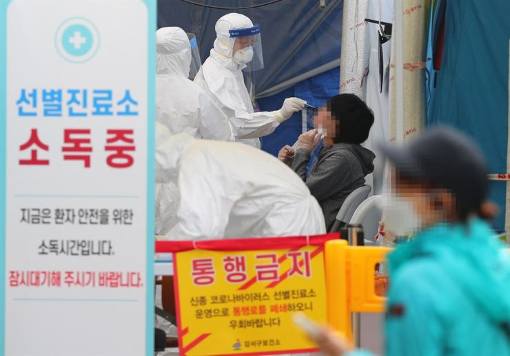 Medical staffers in protective gear conduct the COVID-19 virus test at a public health facility in Seoul, Monday. Yonhap