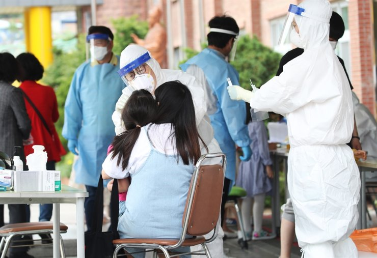 Health officials conduct a coronavirus test on a student at Yangji Elementary School in Anyang, Gyeonggi Province, Sunday, after a student there tested positive for the virus. / Yonhap