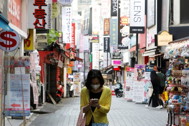 A woman wearing a mask looks at her mobile phone amid social distancing measures to avoid the spread of COVID-19 in Myeongdong shopping district in Seoul, May 28, 2020. Reuters