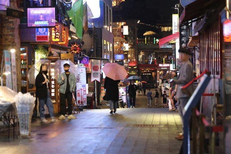 People walk along a street at Itaewon in Seoul, Friday. Yonhap